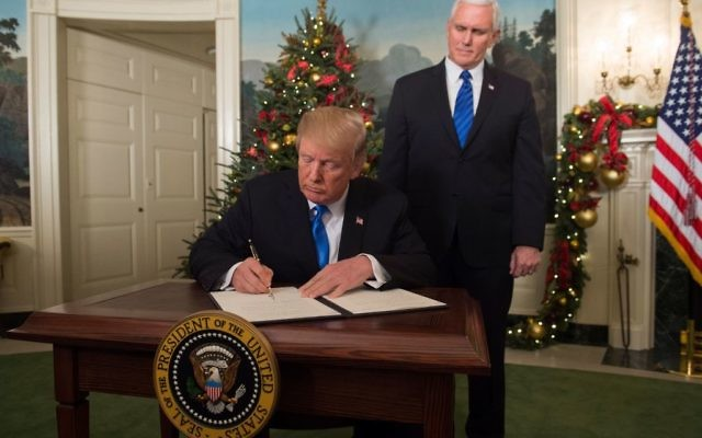 US President Donald Trump signs a proclamation after he delivered a statement on Jerusalem from the Diplomatic Reception Room of the White House in Washington, DC on December 6, 2017 as US Vice President Mike Pence looks on. President Donald Trump recognized the disputed city of Jerusalem as Israel's capital -- a historic decision that overturns decades of US policy. Getty Images