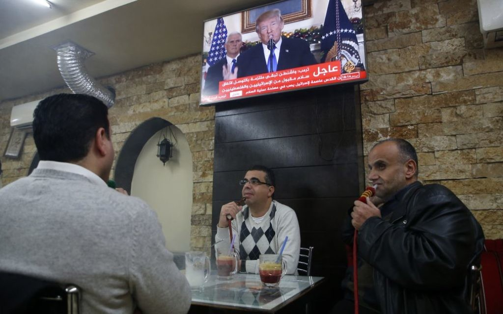 Palestinians sit in a cafe in the West Bank city of Ramallah on December 6, 2017, as TV screens show US President Donald Trump giving a speech in which he announced the recognition of the disputed city of Jerusalem as Israel's capital and his plans to relocate the US embassy there. Getty Images