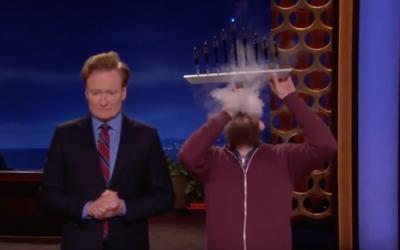 "Conan O'Brien's music producer Roey Hershkovitz, right, demonstrating how to use a vape pen menorah on ""Conan,"" Dec. 13, 2017. (Screenshot from ""Conan"")"