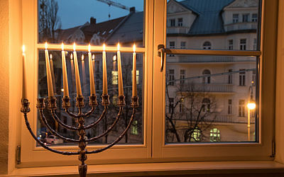 Lighting the menorah across from Hitler's home at Prinzregentenplatz 16 in Munich. The building visible through the window houses the luxury apartment Hitler moved into in 1929. Courtesy of Chabad.org/Mitya Kolomiyets.