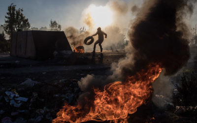 A Palestinian protester pushes a tire onto a fire barricade as they clashed with Israeli border guards near an Israeli checkpoint in Ramallah, West Bank on Dec. 8, 2017. JTA