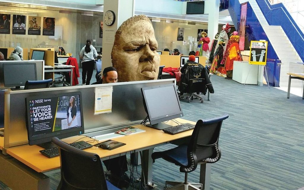 An Orthodox man works at a computer station at Medgar Evers' library, where a bust of rapper Biggie Smalls sits prominently in the center.  Amy Sara Clark/JW