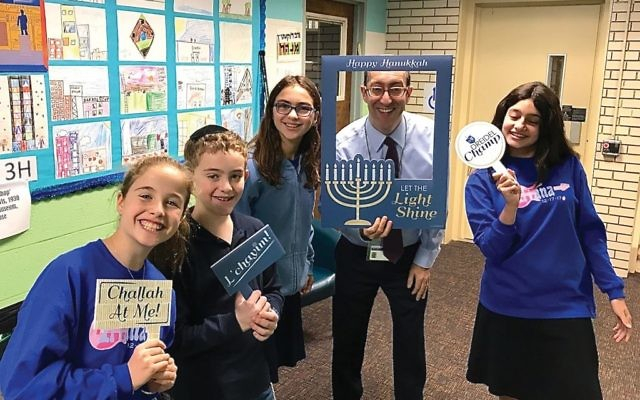 Rabbi Joshua Lookstein with students at Westchester Day School, which is offering what is believed to be the first-of-its-kind community service grant. COURTESY OF WDS