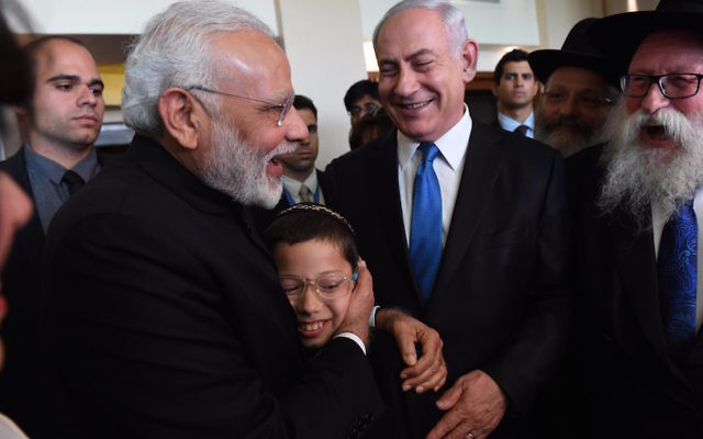 Indian Prime Minister, left, embracing 11-year-old Moshe Holtzberg, whose Chabad emissary parents were killed in a 2008 terror attack in Mumbai, with Israeli Prime Minister Benjamin Netanyahu on left in Israel, July 5, 2017. (Haim Zach/Israeli Government Press Office)