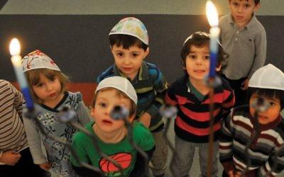 Some Jewish preschoolers in Washington, D.C., gaze at a Chanukah menorah. Mark Gail/The Washington Post via Getty Images