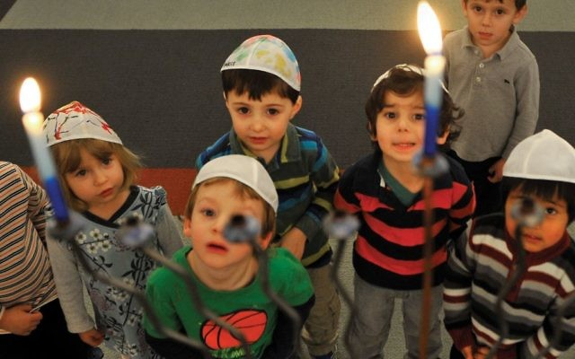 Some Jewish preschoolers in Washington, D.C., gaze at a Chanukah menorah. Mark Gail/The Washington Post via Getty Images