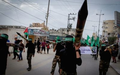 Masked members from the Ezzedine al-Qassam carrying a model of a rocket during a rally to commemorate the 27th anniversary of Hamas' creation in Gaza, Dec. 12, 2014. (Abed Rahim Khatib/Flash90)