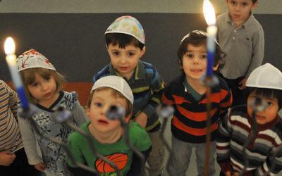 Some Jewish preschoolers in Washington, D.C., gaze at a Hanukkah menorah. (Mark Gail/The Washington Post via Getty Images)