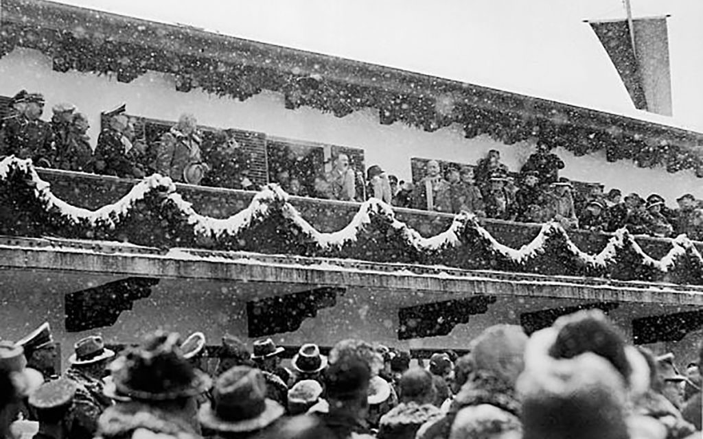 A crowd of spectators at the 1936 Winter Games looks up at the box where Adolf Hitler and other Nazi officials are seated. GETTY IMAGES