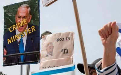 Israeli protestors hold placards critical of Prime Minister Benjamin Netanyahu at a demonstration last week in Tel Aviv. In a new revelation this week, a Netanyahu aide is suspected of bribing a judge to go easy on Sara Netanyahu. JACK GUEZ/AFP/Getty Images