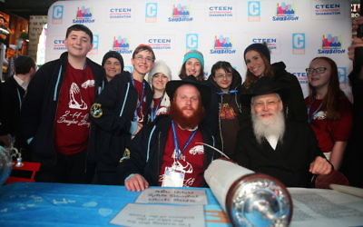In center, with the red beard, Rabbi Shaya Denburg, co-director of CTeen in Coral Springs, Fla., with Rabbi Moshe Klein on his right; Chayale Denburg, co-director of CTeen in Coral Springs, Fla., who is standing and second from right; and some survivors of the Parkland, Fla. school shooting. The survivors were in New York this weekend for Chabad's CTeen conference. (Itzik Roytman/Cteen)