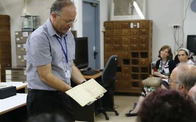 Yad Vashem Archives Director Dr. Haim Gertner holding a Holocaust-era document Yad Vashem