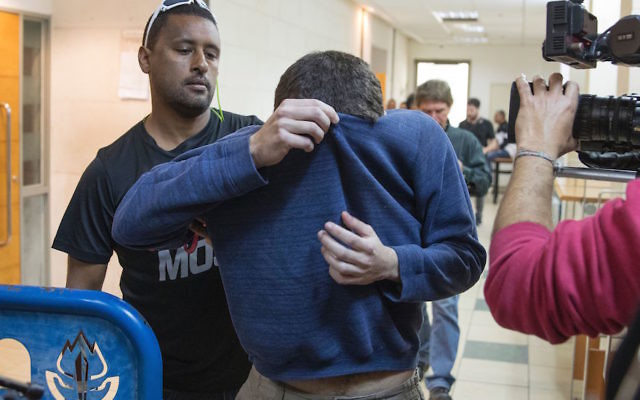 Michael Kadar, an American-Israeli man accused of making dozens of anti-Semitic bomb threats in the United States and elsewhere, is escorted by guards as he leaves an Israeli court in Rishon Lezion on March 23, 2017. (JACK GUEZ/AFP/Getty Images)
