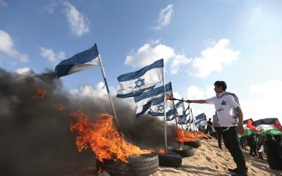 Palestinian protestors prepare to set fire to Israeli flags at the Israeli-Gaza border during recent clashes. MOHAMMED ABED/AFP/Getty Images