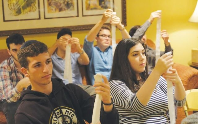 "Students at Boca's Katz Yeshiva learn to tie the intricate ""shin knot"" used on the traditional burial clothing and prepare for purifying a body for burial. Photos by Claudia Cohen"