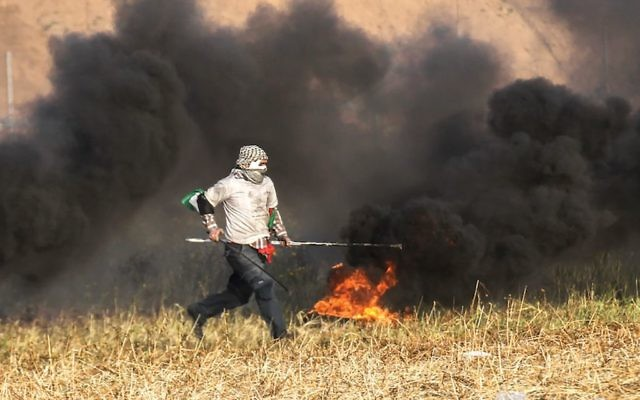 A Palestinian protester burning tires during clashes Monday with Israeli forces near the border of the southern Gaza Strip. Getty Images