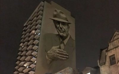 A painting of Leonard Cohen towers above Crescent Street in downtown Montreal. Ben Harris