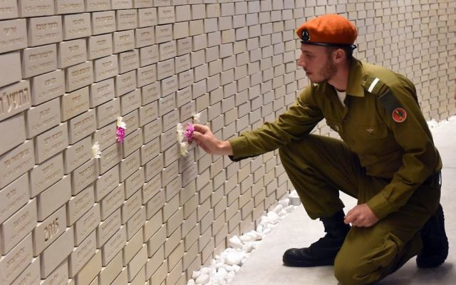 An Israeli soldier places a flower on the name of a fallen soldier in the National Memorial Hall For Israel's Fallen before the official ceremony for Israel's Remembrance Day in the Mt. Herzl Military Cemetery in Jerusalem on April 18, 2018. Getty Images