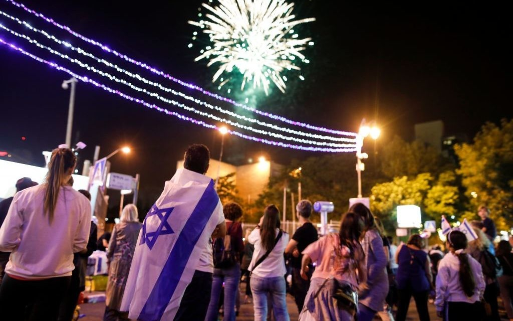 Israeli youths watch fireworks over the centre of Jerusalem late on April 18, 2018, during the conclusion of Memorial Day and the start of the 70th Independence Day celebrations. Getty Images
