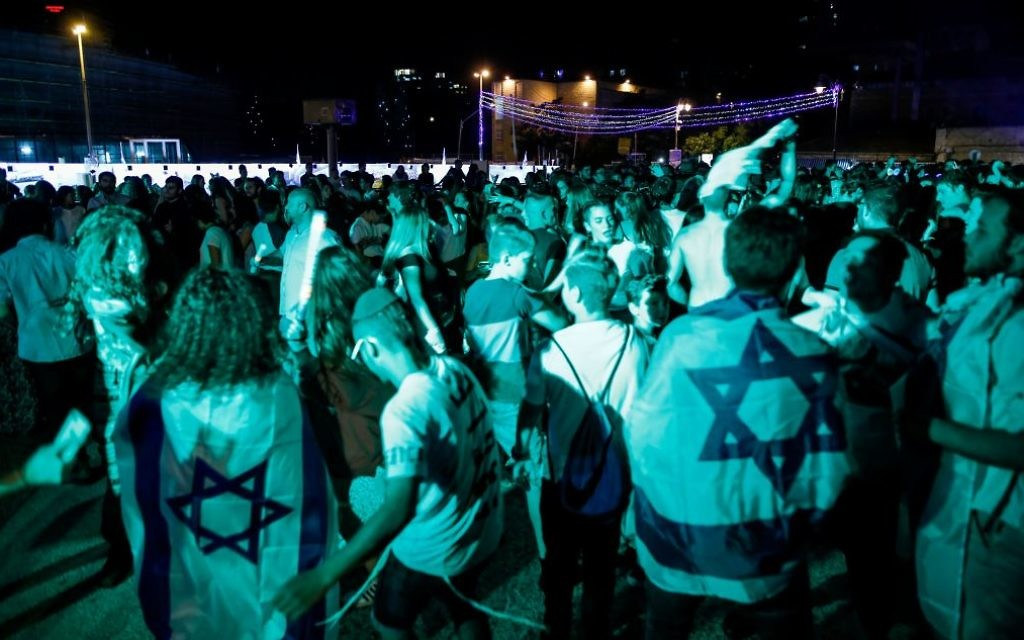 Israeli youths draped in Israeli flags dance in a square in the centre of Jerusalem late on April 18, 2018, during the start of the 70th Independence Day celebrations. Israel's national day, also known as Yom Ha'atzmaut, commemorates the country's declaration of independence in 1948. Getty Images