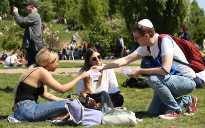 A volunteer handing out kippahs to visitors at the Mauerpark in Berlin, April 29, 2018. (Adam Berry/Getty Images)