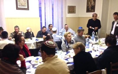 Jewish Week Staff Writer Steve Lipman, standing, in dark sweater, leads the community seder. Steve Lipman/JW