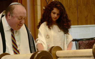 Minnah Stein on her Bat Mitzvah day, reading from the Torah with her Rabbi. Courtesy of Minnah Stein.