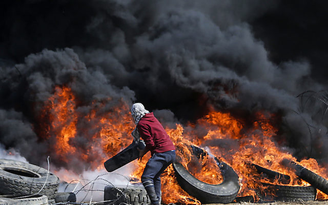 A Palestinian protestor burning tires during clashes with Israeli forces on the Israel-Gaza border, east of Gaza City in the central Gaza Strip, April 27, 2018. JTA