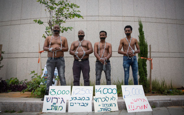 African asylum seekers set up a mock slave auction as part of a protest outside the Ministry of Defense in Tel Aviv, April 3, 2018. (Miriam Alster/Flash90)