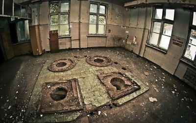 Only holes in the floor of one-time toilets remain on the grounds of Nazi-era hospital in Legnica, Poland.  JAKUB PUREJ