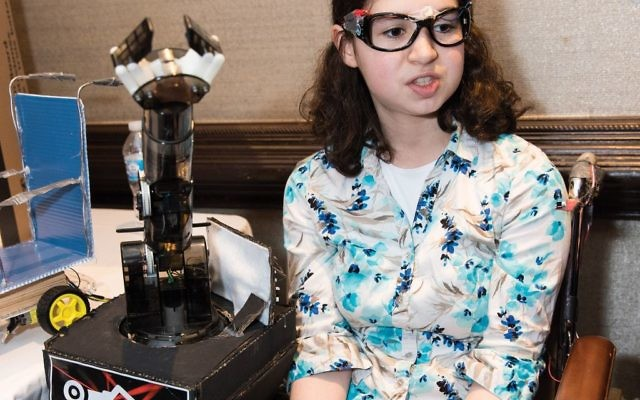 "Chana Schwartz, a Bruriah 11th-grader, demonstrates the ""Care Chair,"" the project she developed with Adina Strong and Adina Weisel. Photo by Eli Weintraub Photography"