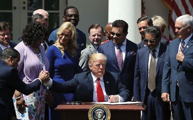 President Donald Trump, flanked by members of faith-based communities, signs a proclamation declaring a National Day of Prayer during an event May 3 in the White House Rose Garden. Mark Wilson/Getty Images
