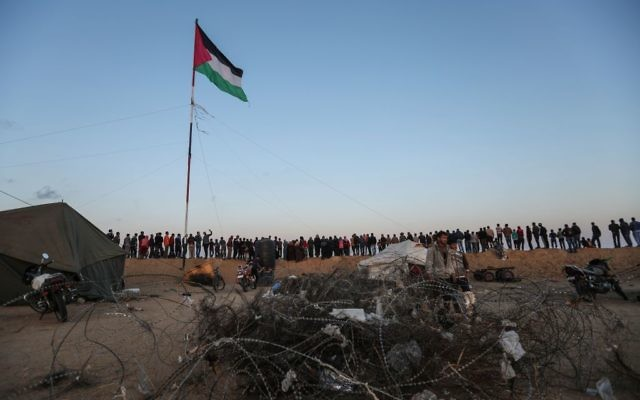Palestinian protestors stand under their national flag as they demonstrate near the southern Gaza Strip. Getty Images.