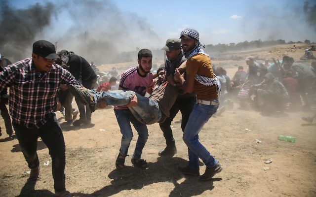 Palestinians carrying a wounded man during a protest against United States' plans to relocate its embassy from Tel Aviv to Jerusalem, near Al Bureij Refugee Camp at the Gaza-Israel border, May 14, 2018. (Hassan Jedi/Anadolu Agency/Getty Images)