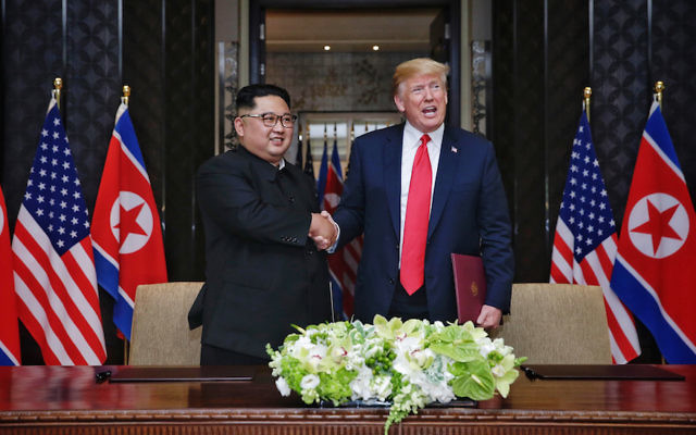 North Korean leader Kim Jong Un and President Donald Trump shake hands at their historic summit in Singapore, June 12, 2018. (Kevin Lim/The Strait Times/Handout/Getty Images)
