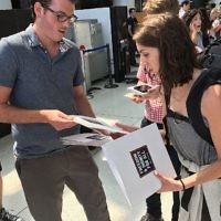 An IfNotNow member distributes materials to a Birthright participant in New York's JFK airport, Monday, June 18, 2018. (Steven Davidson via Times of Israel)
