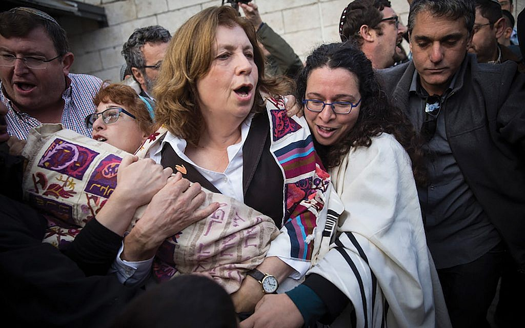 Holy rift: One of the causes for increased  tensions among progressives and the conservative groups in Israel is the battle over egalitarian prayer at the Western Wall. Above, Anat Hoffman, a leader of Women of the Wall, carrying a Torah near the Kotel, leading to her arrest. JTA