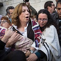 Holy rift: One of the causes for increased diaspora-Israel tensions is the battle over egalitarian prayer at the Western Wall. Above, Anat Hoffman, a leader of Women of the Wall, carrying a Torah near the Kotel, leading to her arrest. JTA