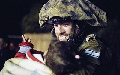 An Israeli soldier rescuing a child belonging to a family of White Helmet volunteers. The Syria Civil Defense volunteers came under fire last weekend in the ongoing Syrian civil war. IDF Photo