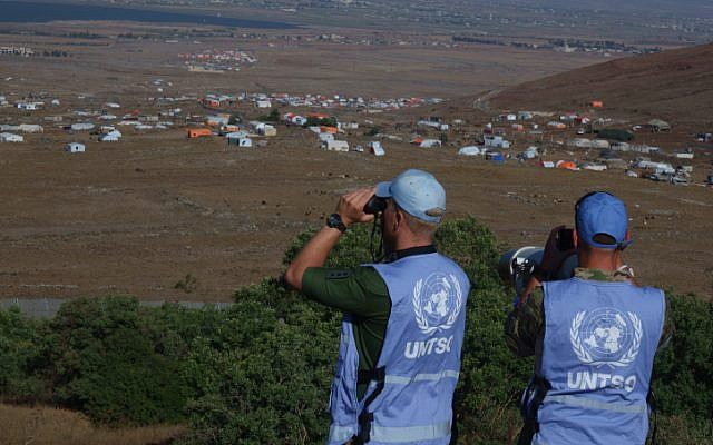 United Nations workers standing on the Israeli side of the Golan Heights monitor a Syrian refugee camp in Quneitra province on the Syrian side of the Israeli-Syrian border on July 17, 2018. JTA