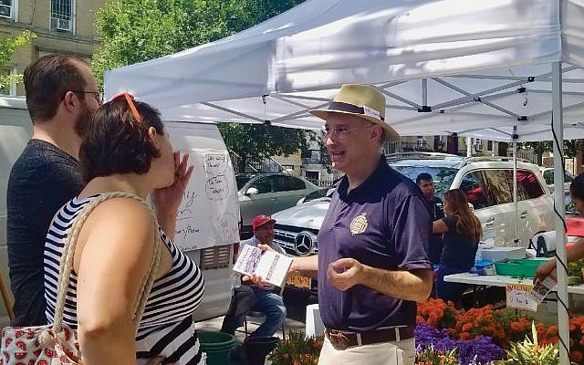 Attorney Blake Morris campaigning to unseat state Sen. Simcha Felder at a farmers' market last month. Courtesy of Blake Morris for NYS Senate District 17