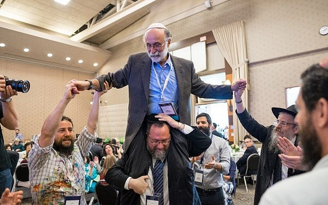 Robert Meeropol and Rabbi Efraim Mintz dance at a conference of the Rohr Jewish Learning Institute. (JTA)