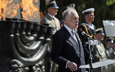 Ronald Lauder speaking next to a lit menorah at a memorial to the Warsaw Ghetto Uprising in Poland, April 19, 2018. (JTA)