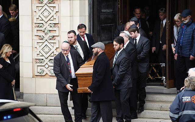 Caskets of the Rosenthal Brothers, Cecil 59, and David, 54, are carried out of Rodef Shalom Temple Tuesday in Pittsburgh. They were killed in the Tree of Life synagogue massacre. Getty Images