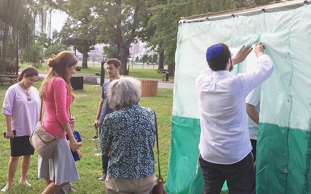 Rabbi Choli Mishulovin, invites people into a sukkah on Randall's Island. Courtesy of Dan Whateley