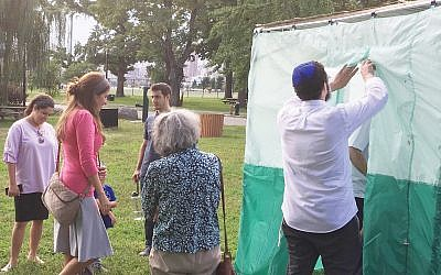 Rabbi Choli Mishulovin, invites people into a sukkah on Randall's Island. Courtesy of Dan Whateley