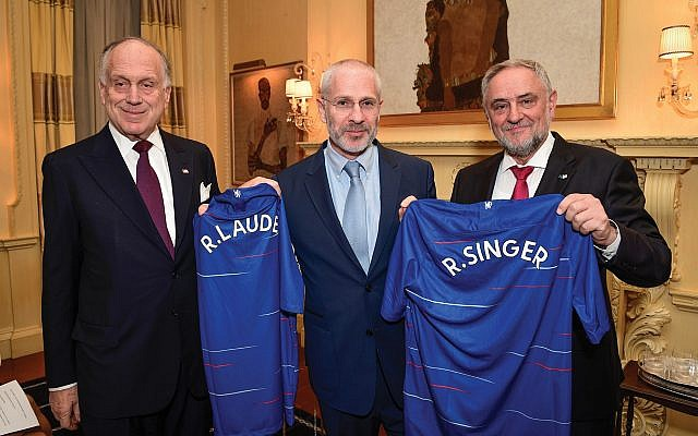 Chelsea Football Club director Eugene Tenenbaum, center, presents World Jewish Congress officials Ronald Lauder, left, and Robert Singer with Chelsea's iconic blue jersey. Courtesy of WJC