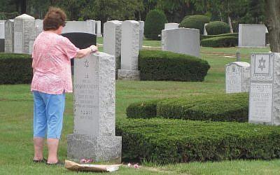 Part of a gravesite visit program sponsored by Plaza Jewish Community Chapel and the Marlene Meyerson JCC Manhattan, Joy Yagman touches her father's memorial stone. Photos by STEVE LIPMAN/JW