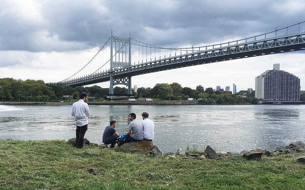"""Rabbi Mishulovin, left, at a """"Sukkah Fest"""" event last month along the East River. Courtesy of Dan Whateley"""