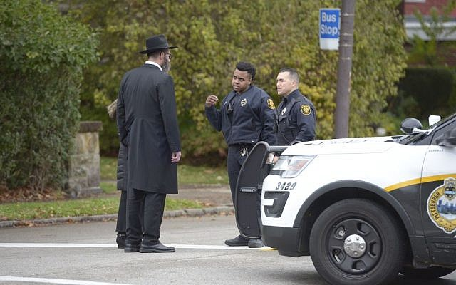 Police speak with members of the community after a shooting at the Tree of Life Synagogue at Squirrel Hill, Pennsylvania on October 27, 2018. - A synagogue shooting in Pittsburgh has left at least 11 people dead and several more wounded, several US media said, an attack the US president has condemned as anti-Semitic. (Photo by Dustin Franz / AFP)        (Photo credit should read DUSTIN FRANZ/AFP/Getty Images)